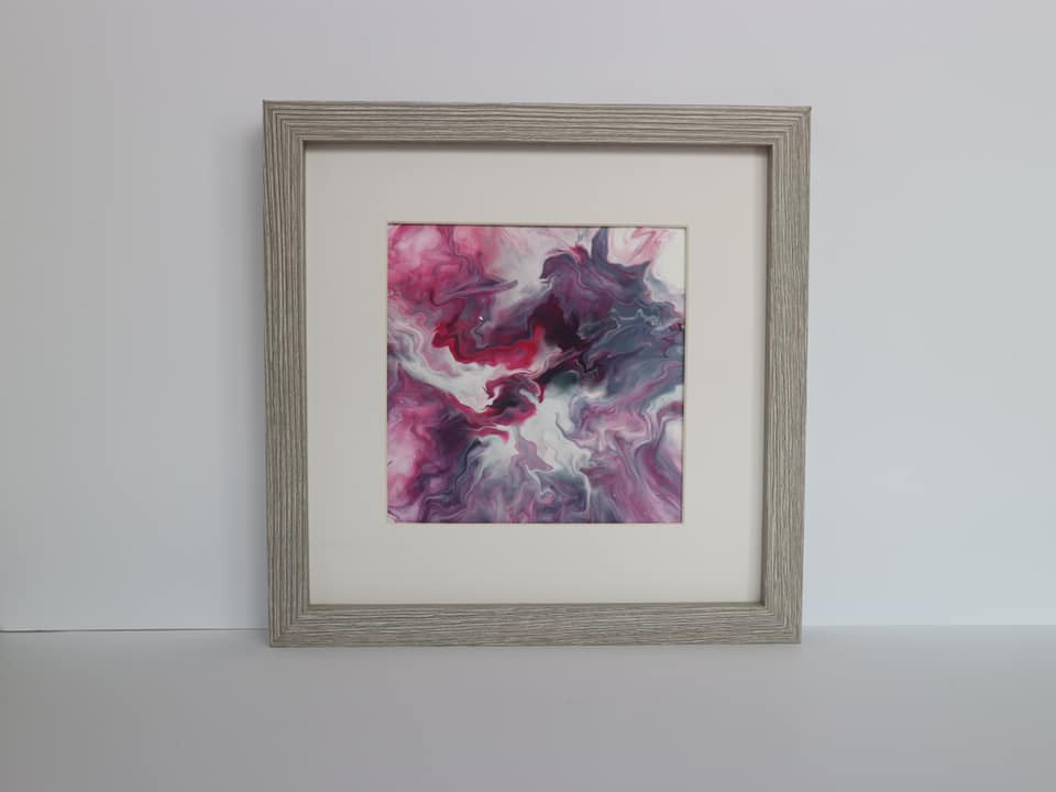 An abstract painting on paper, in a mount and wood-effect grey frame. The painting is a wispy pattern of grey and pink moving outwards from the centre of the canvas, against a white background.
