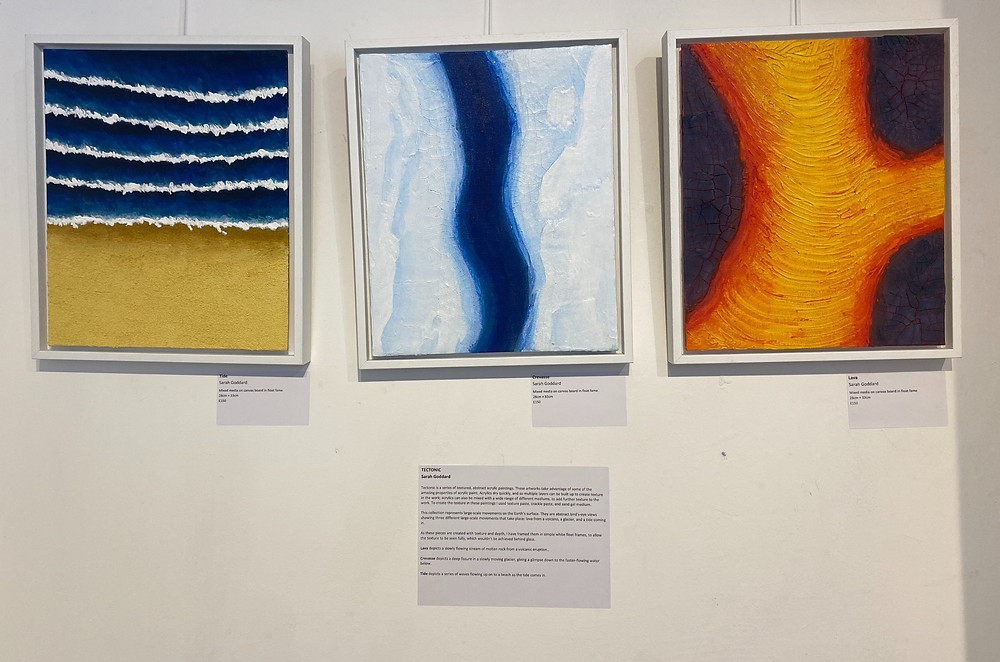 Image shows three paintings in white float flames. From left to right: Tide - a textured painting of sand with ocean and waves above it; Crevasse - a textured painting of the ice of a glacier, with a crevasse running through the centre showing blue water below it; Lava - a textured painting of yellow-red lava flowing through grey rock.