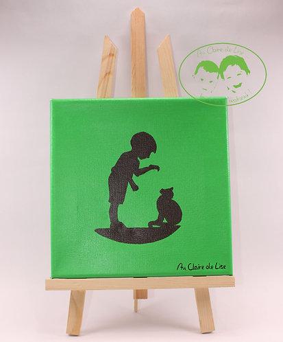 Tableau vert pomme et silhouette noire petit garçon qui récompense un chat.
