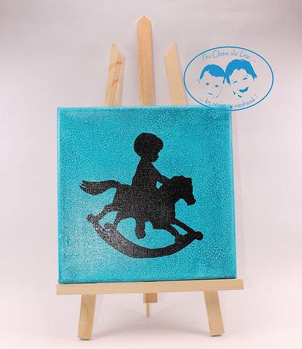Tableau turquoise silhouette petit garçon sur son cheval à bascule