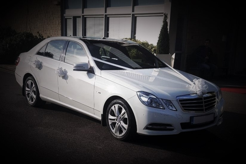 wedding car with white ribbons