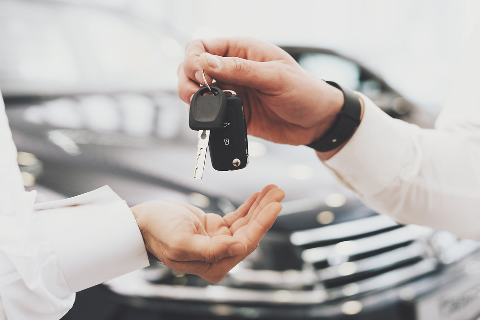 Salesman is giving keys for new car to m