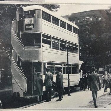A triple-decker bus roaming the streets of Berlin, Germany.