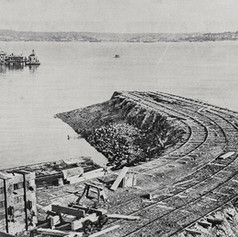 Construction of the Takapuna tramway, Auckland: the embankment and commencement of the wharf at O'Neil's point. Showing the city and harbour in the background. 1909