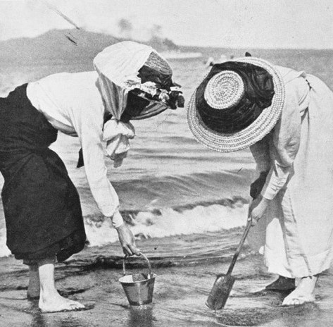 Two women digging in the sand on Takapuna Beach, Dec 1910