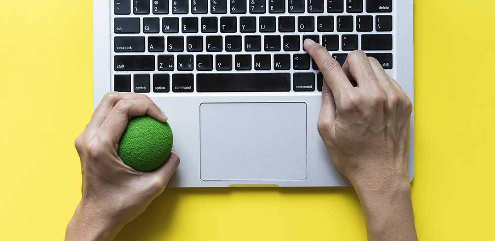 laptop with two hands, one holding a stress ball: The Parents' Guide to