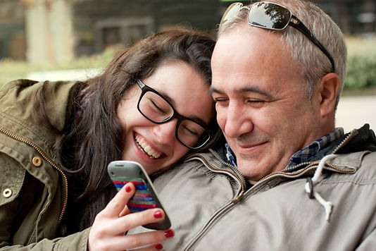 Father and daughter hugging smiling and looking at mobile phone: The Parents' Guide to
