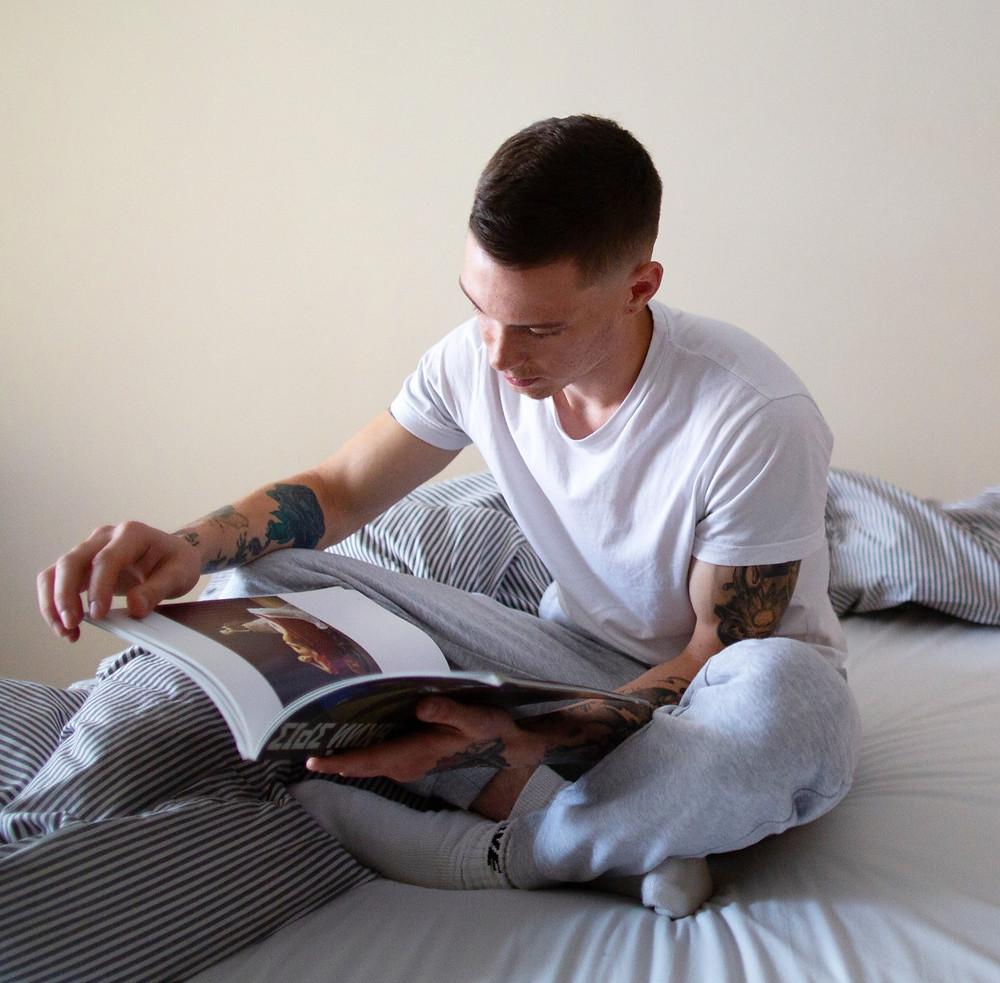 Teenage boy reading on bed