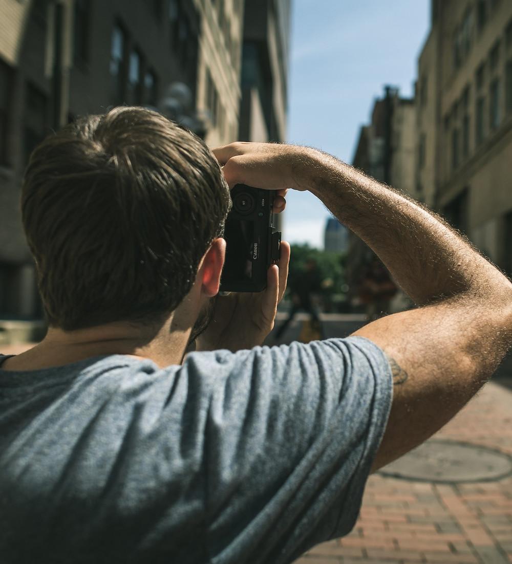 Teenage boy with camera taking a photo of UK highstreet