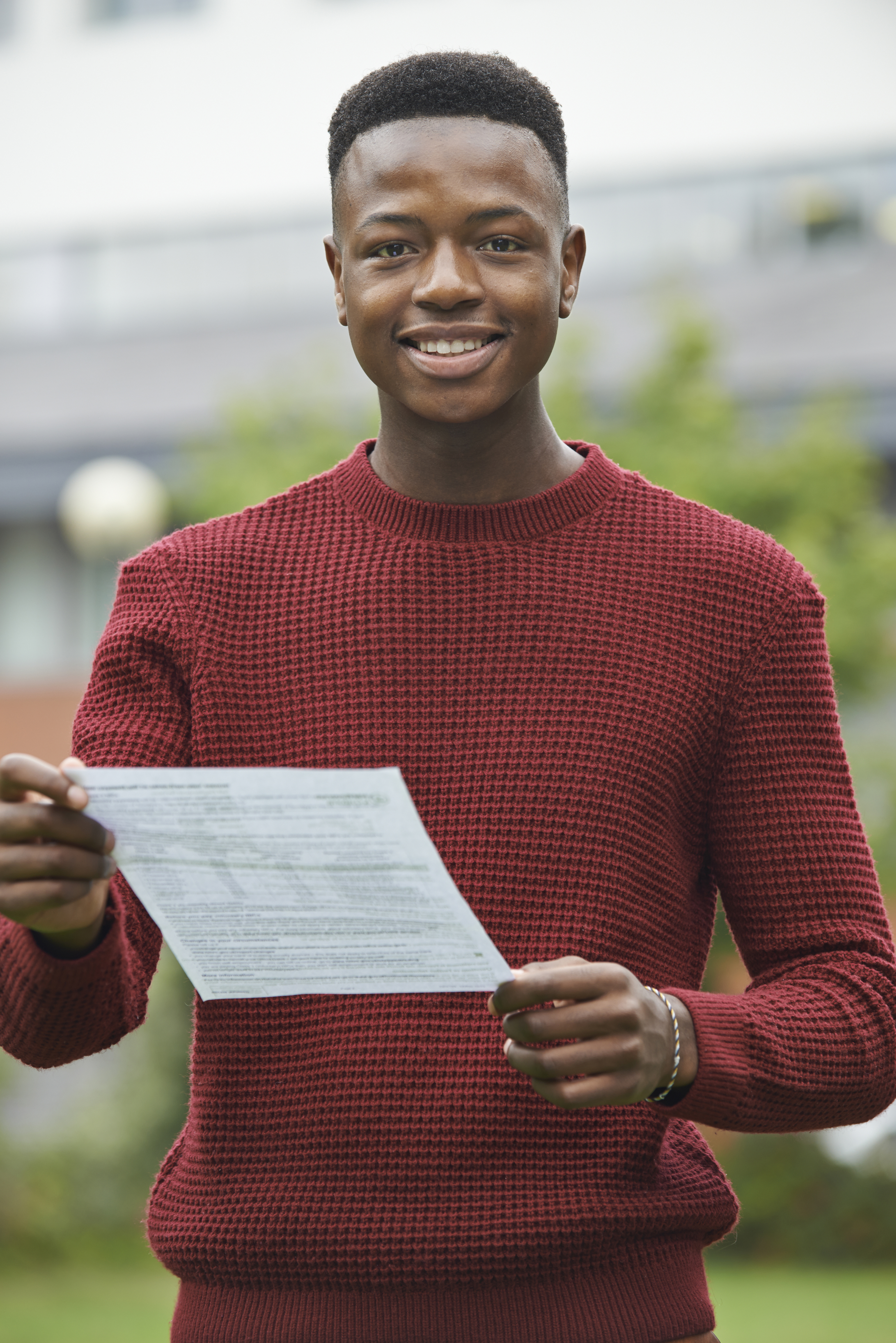Male teenage student on results day, smiling whilst looking at their A level grades.