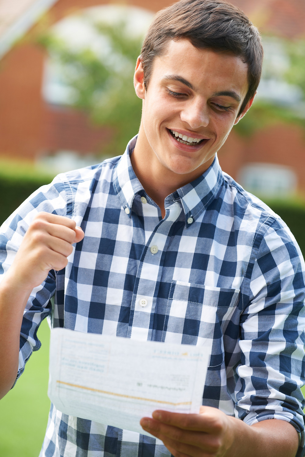 Teenage boy celebrating good a level results on results day 2020, excited