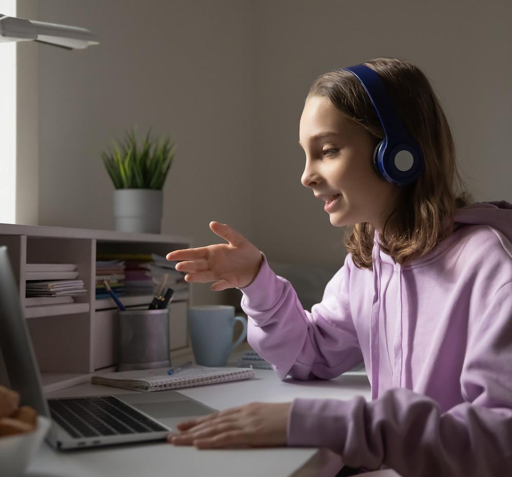Teenage girl with headphones on laptop