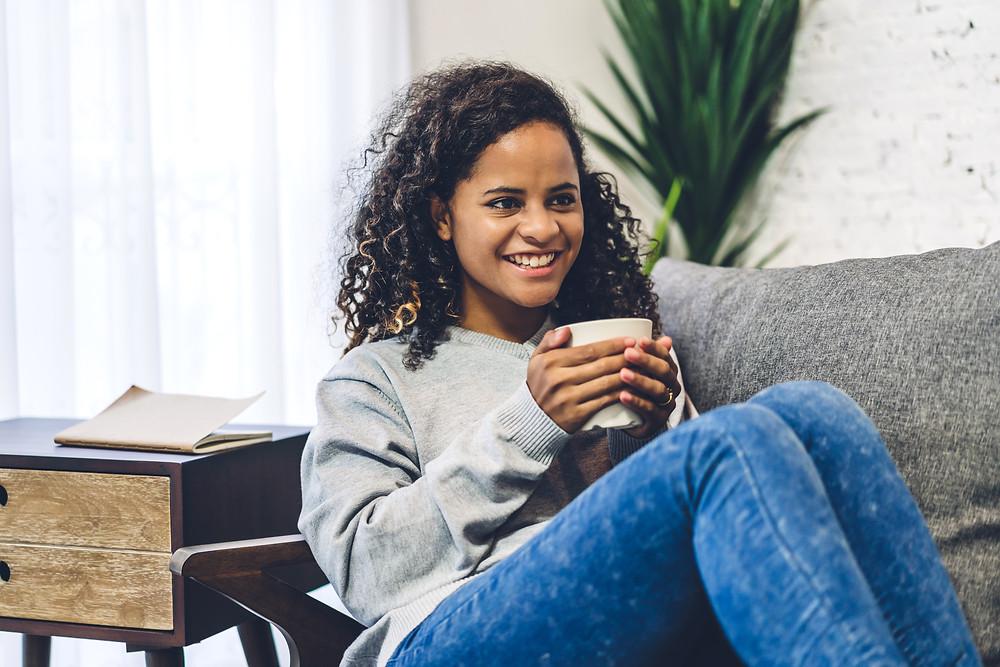 Teenage girl sipping coffee and laying down on sofa