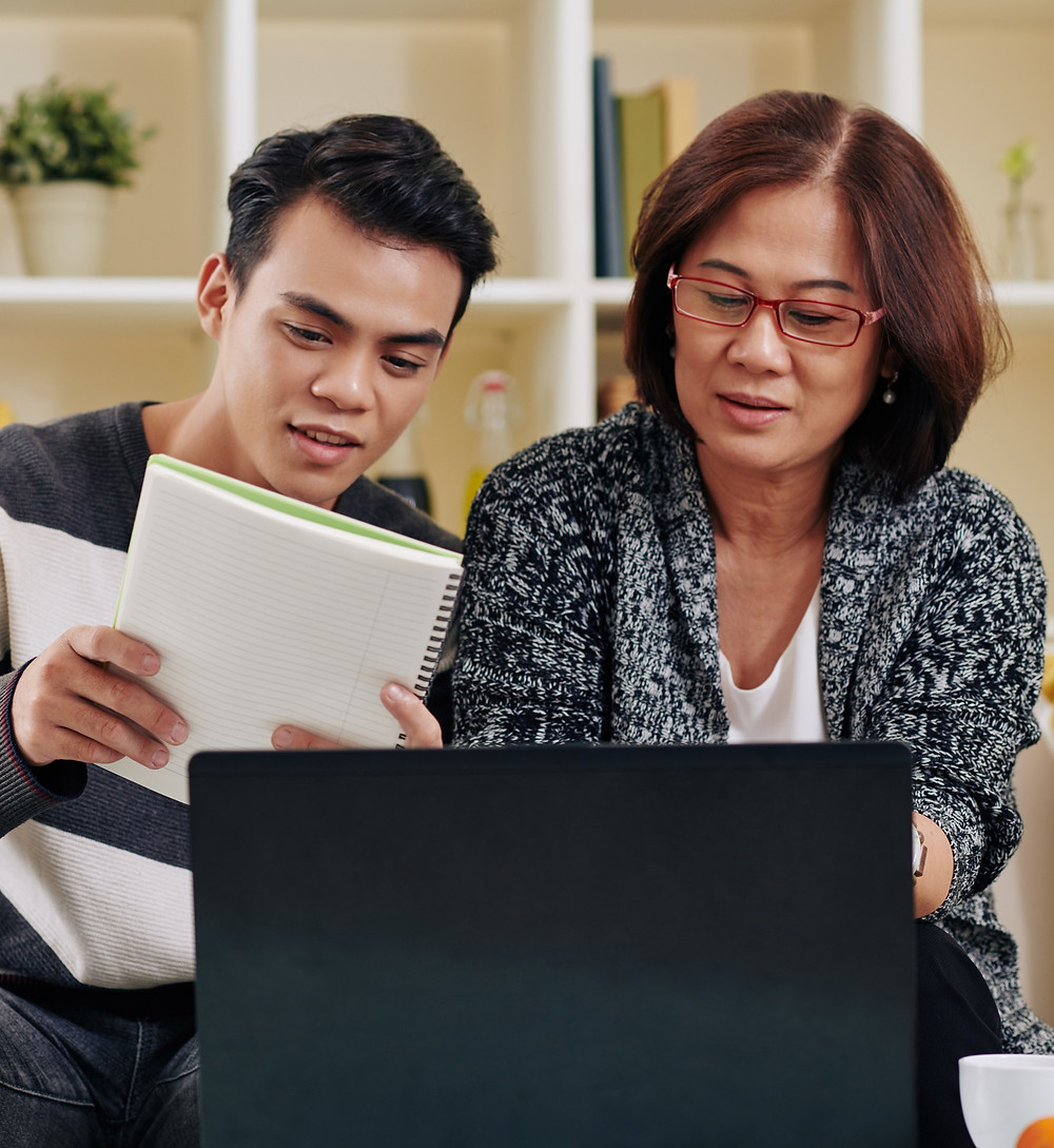 Asian mother and teenage son applying to university computer UCAS living room home The Parents Guide to