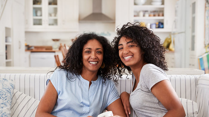 Mother and daughter sitting on sofa smiling: The Parents' guide to