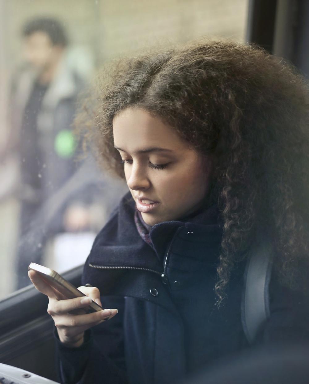 Teen girl on bus using mobile phone
