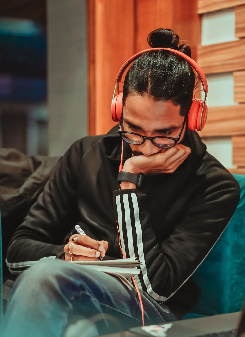 Male teenager listening to music and writing in journal