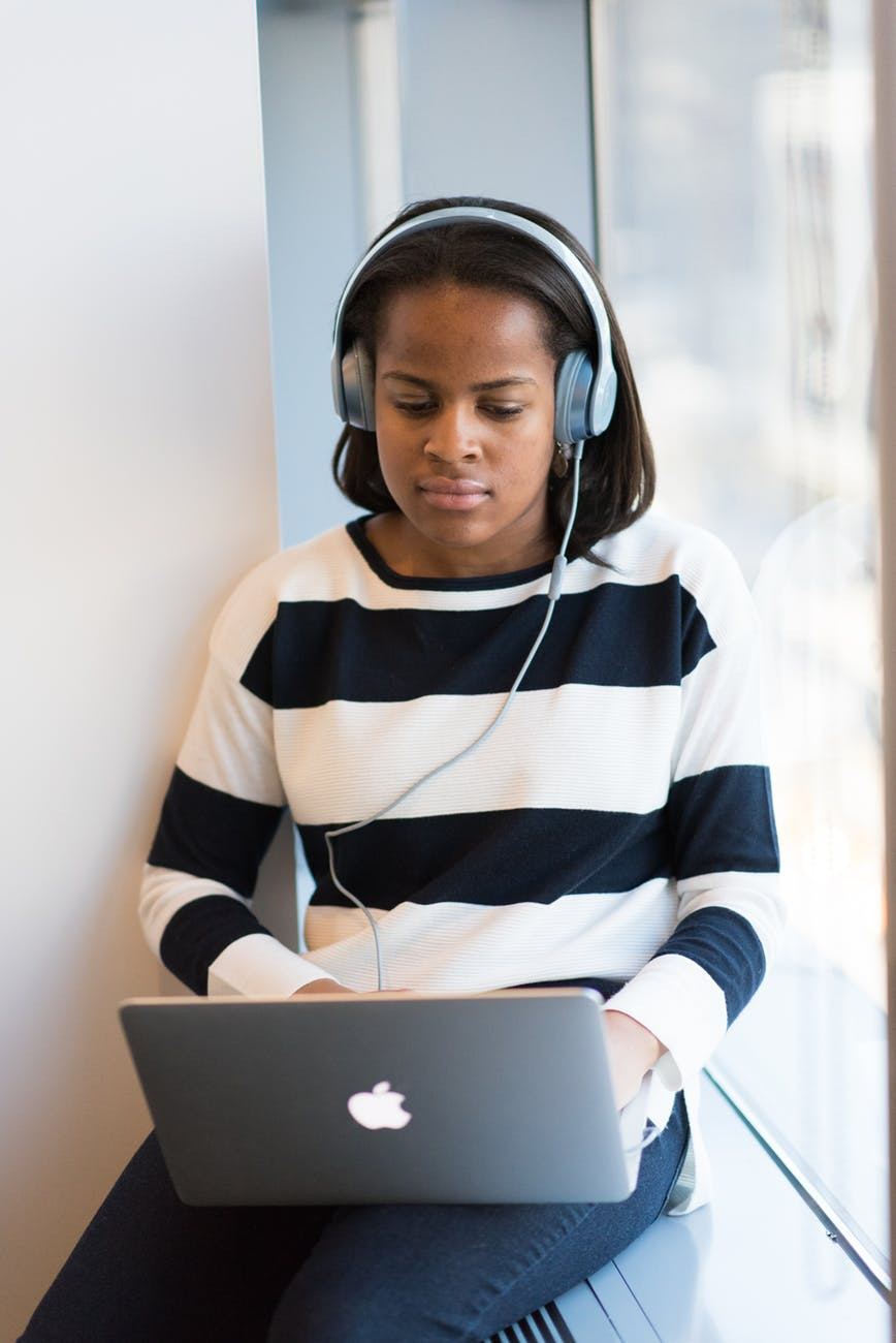 Femal teen student sitting and listening to a podcast with headphones and a laptop The Parents' Guide to stand out