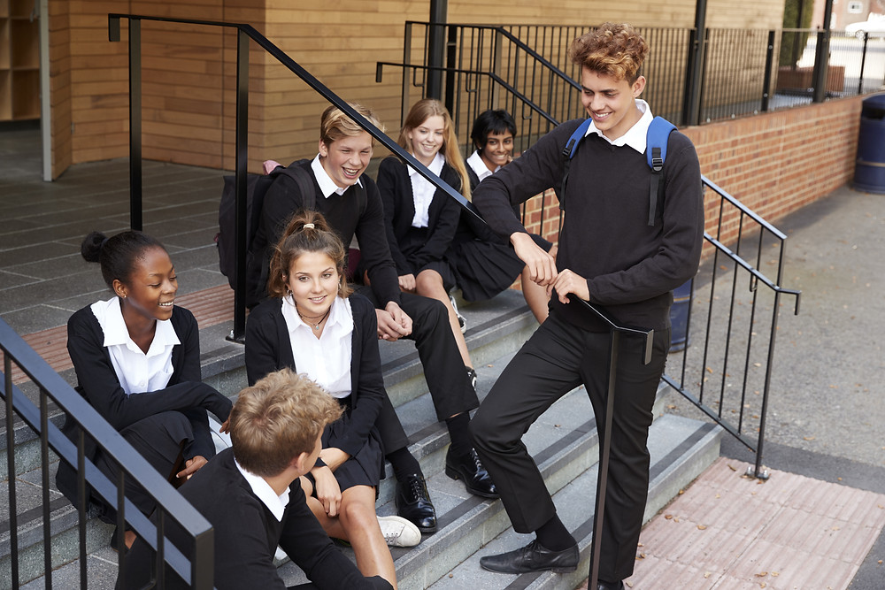 Group of secondary school students sitting on stairs of the entrance to school chatting