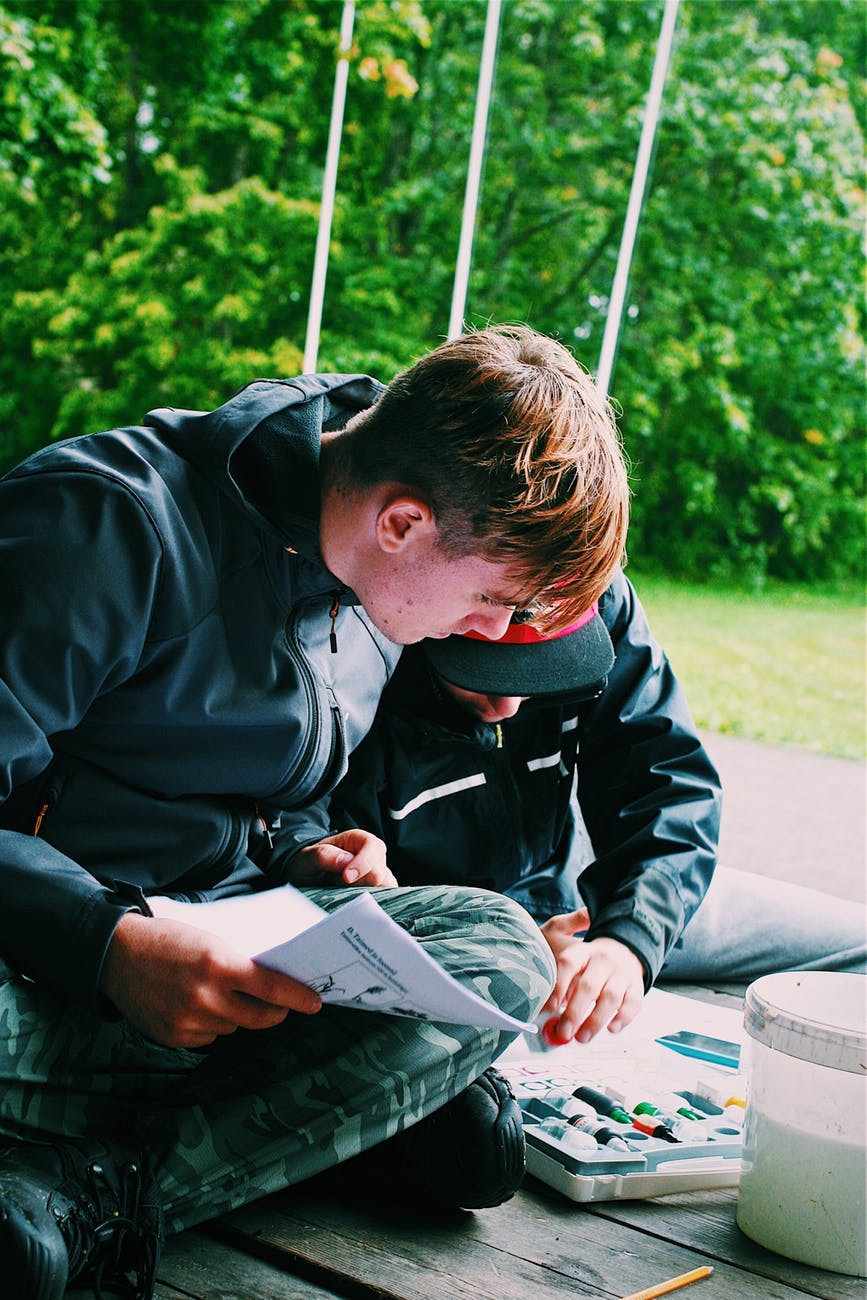 Two teenage boys outside looking at map and studying together