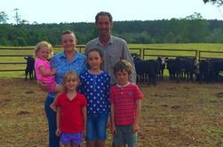 HighBrit family in front of Angus weaners in the yards.