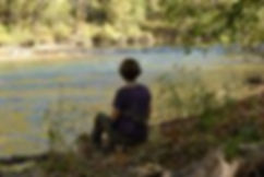 Photo of Meditator sitting quietly by the Powell River at Well Being Retreat Center