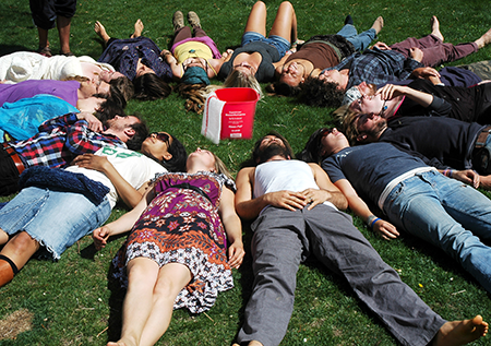 A bunch of students lying on the grass in a circle. A red sanitizer bucket and wash rag sit unassumedly in the middle.