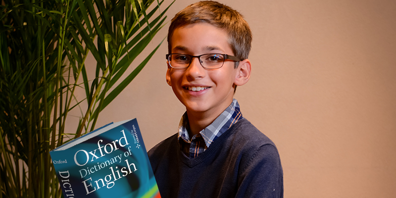 Young boy with glasses, wearing a sweater, holds a dictionary. Fake plants are off to the left.