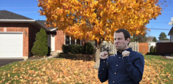 A tree drops leaves on the lawn before a suburban house. A man in the foreground clenches his fists in anger.