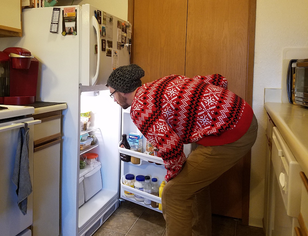 Man forages for food in the fridge