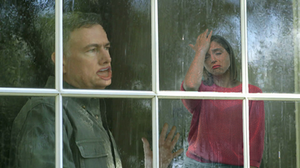 A woman cries while her husband looks out the window, yearning.