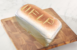 """A bread sits on a cutting board. """"HELP"""" is scored into the top of the loaf."""
