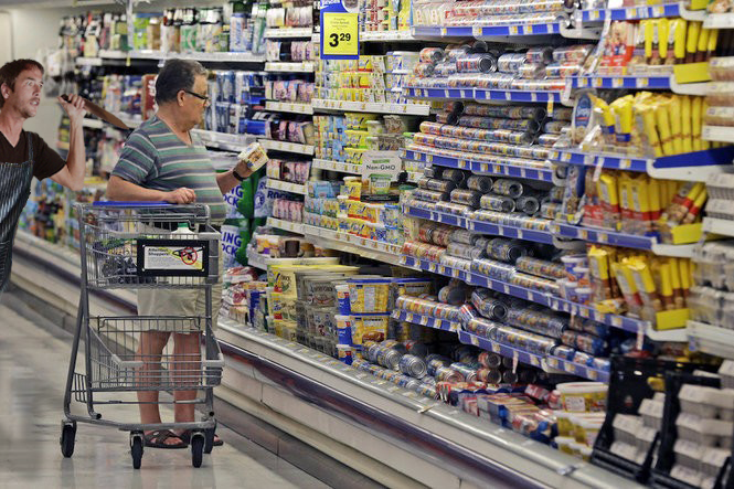 A shopper peruses butter alternatives. A store employy stands behind them, wielding a knife.