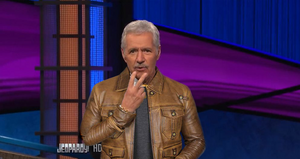 Alex Trebek in a leather jacket, making the peace sign.