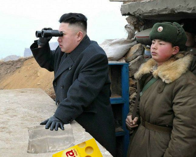 Kim Jong-un looks through binoculars for more Nella Wafers. An emprty Nella Wafers box lays beside him.