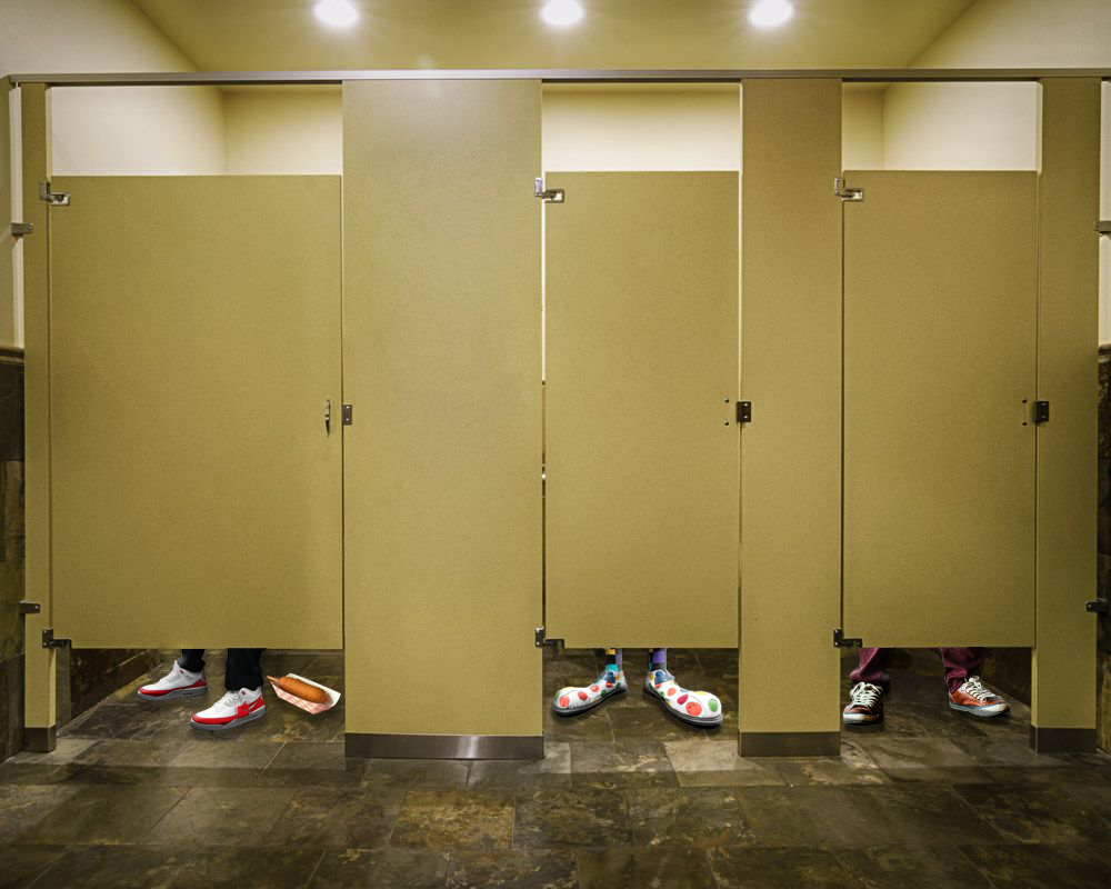 3 pairs of feet sit behind 3 different bathroom stalls. The left stall also has a corndog on the floor. The middle stall shows clown shoes.