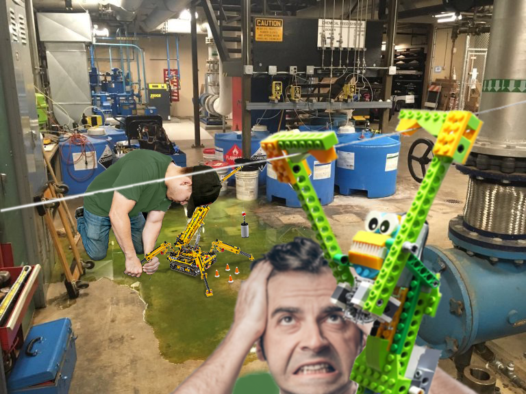 A green liquid is spilled out on the floor of a maintenance area. A worker kneels in the liquid, working on a LEGO Tehcnic crane. A different man appears frustrated as a LEGO Technic monkey crosses a string before him.