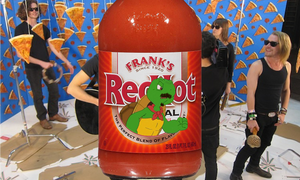 Franklin Turtle looks a bit angry on the wrapper of a bottle of Frank's Red Hot. He has a mustache and goatee, and his ascot is torn. The Pizza Underground is in the background.