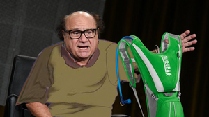 Danny DeVito dressed as Quasimodo holds up a green Camelbak backpack