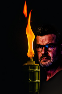 Man stares ominously at a lit bamboo tiki torch illuminating the darkness.