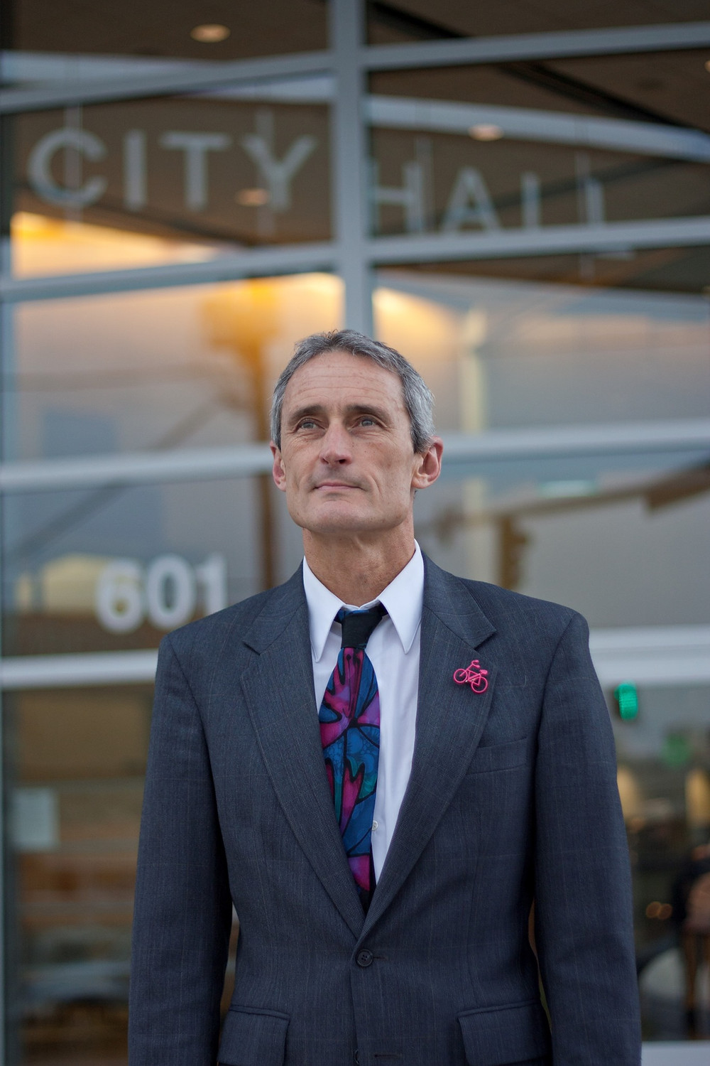Steve Hall, retired city manager, stands in front of City Hall in Olympia Washington, wearing a suit and colorful stained-glass-like tie.