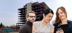 The skeletal Views on Fifth construction zone looms in the background while a dude with glasses looks on at two folks who didn't hear the dude's statement.
