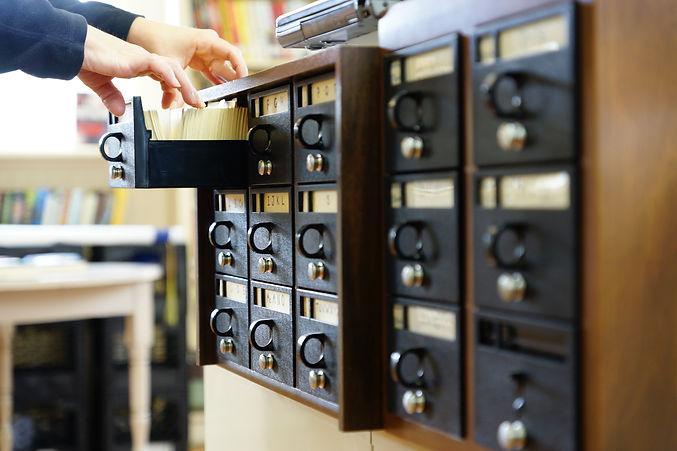 Hands flipping through a card catalogue