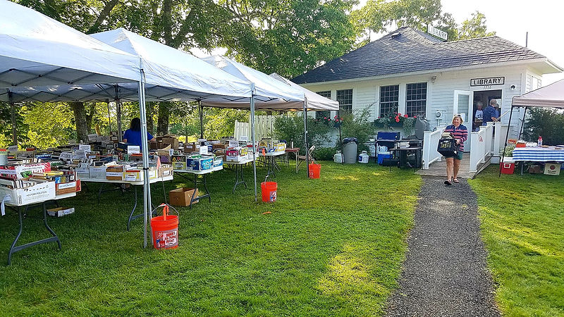 Outdoor book sale with tents, boxes of books, and people