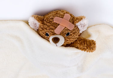 Teddy bear with bandaid on, tucked into bed