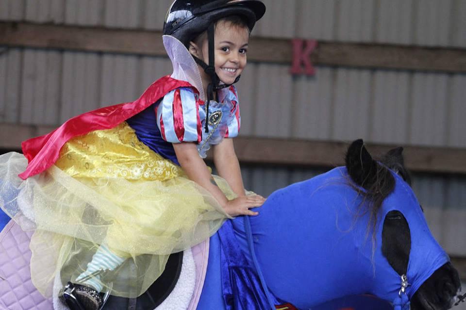Talia Cisneros, 4, of Eugene, rides Tessa, a Shetland pony dressed as Superman