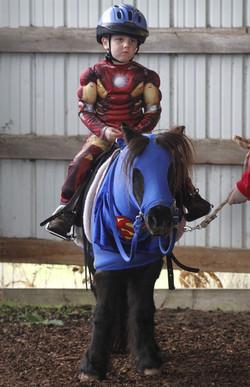 Iron Man, aka Tommy Adams, 4, of Eugene, is ready to ride Tessa, a Shetland pony dressed as Superman
