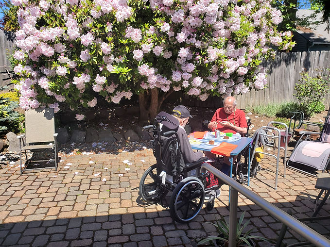 Two of our residents enjoying lunch outside under a flowering tree in our backyard.