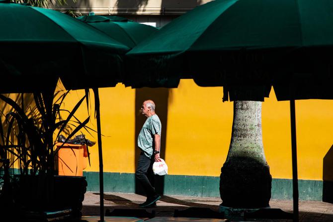 Foto horizontal colorida. Ambiente ensolarado, ao fundo uma parede amarela, cerca de 30 centímetros de sua base é pintada de verde. Do lado direito um caule de palmeira e do esquerdo uma lixeira laranja. No primeiro plano, em área de sombra, guarda-sóis verde escuros abertos emolduram a parte superior da cena. Próximo à parede, bem ao meio, um homem de perfil caminha da direita para esquerda. Ele é calvo, com pouco cabelo grisalho nos lados e atrás da cabeça. Ele veste calça escura, camiseta clara estampada, carrega uma sacola plástica branca e expele fumaça pela boca.