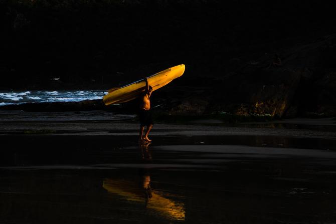 Foto horizontal colorida. Praia sob a pouca luz dos últimos raios do pôr do sol. Ao fundo percebe-se ainda a espuma branca formada pelas ondas do mar. No meio, sob uma luz tênue amarelada, um homem sai do mar e carrega no ombro um caiaque amarelo e seu remo. Ele está de bermuda preta, sem camisa e é visto de perfil, caminhando da esquerda para a direita em uma área onde a água do mar ainda alcança. A camada fina de água sobre a areia reflete sua imagem no chão, com destaque para a cor do caiaque.